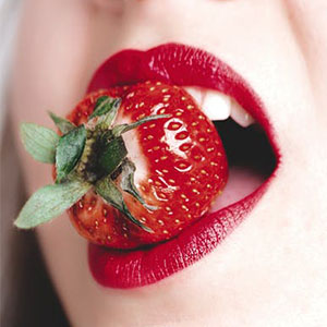 Sexy women holding strawberry in mouth